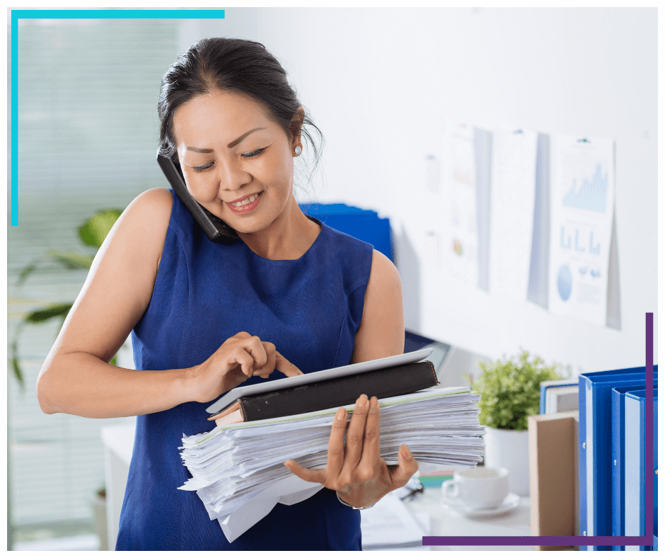 Business woman talking on the phone, holding onto a ton of paper and using digital tablet